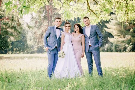 Bride and groom with friends in the park