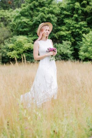 Beautiful young woman in a white vintage lace dress with pink hair and a hat walks across the meadow