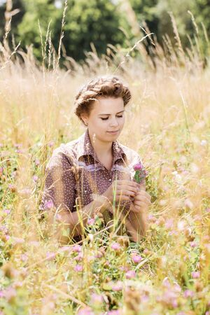 The girl in the field collects a bouquet of clover