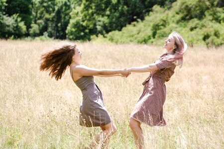 Two young beautiful cheerful girls having fun on the meadow in the park Archivio Fotografico