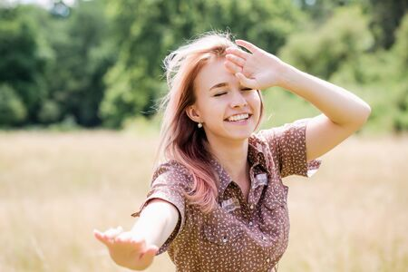 Young beautiful woman in a country style dress on the field Stock Photo