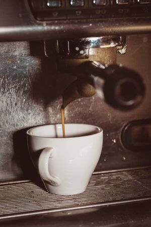 Coffee brewed in a coffee machine pours into the cup