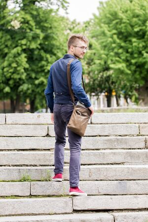 Young handsome man in glasses with a beard and a bag climbs up the stairs Stock Photo