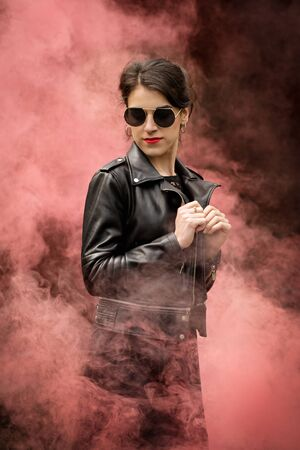 Beautiful woman in a leather jacket and sunglasses in red smoke