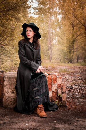 Woman in a black cloak and hat sits on the old ruins Banco de Imagens