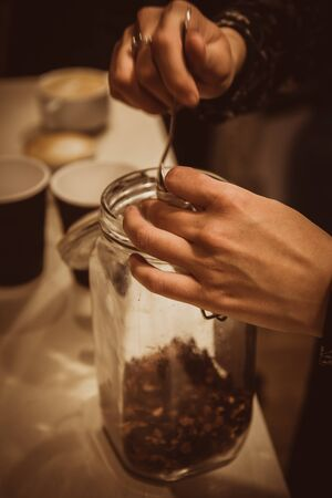 Woman takes tea from a glass jar