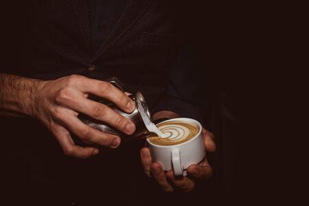 Barista makes flavored cappuccino, pours milk into coffee Imagens - 131219394