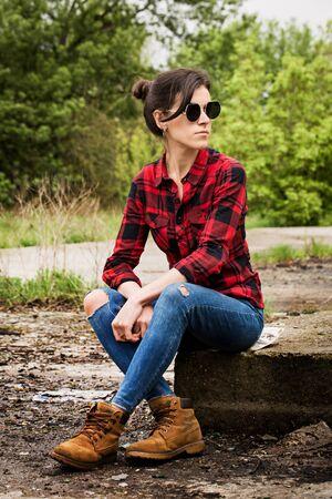 Jong mooi meisje zittend op een betonnen paneel op een verlaten plek Stockfoto