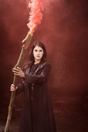 Beautiful witch in black with a smoking stick. Halloween concept
