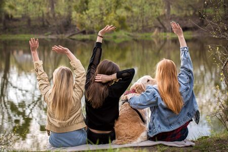 Three girls relaxing by the river with a dog