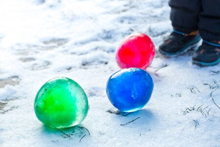Multi-colored ice balls in the snow on a sunny winter day
