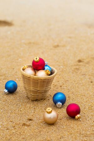 Christmas balls in a basket on the sandy shore of the ocean