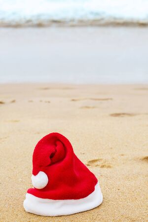 Santa hat on the sandy ocean. Christmas concept