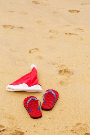 Santa hat and shoes on the sandy ocean. Christmas concept