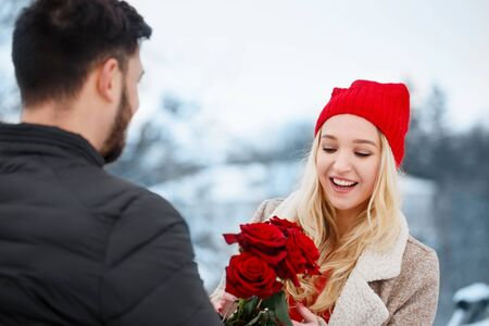 Young beautiful couple with red roses outdoors in snowy weather Foto de archivo - 138047533