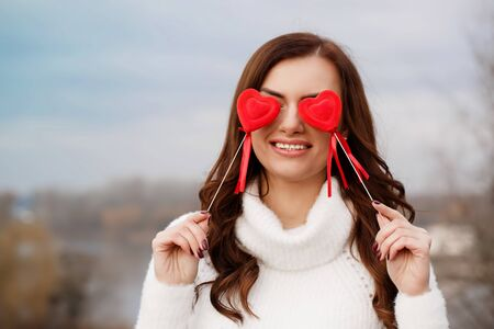 Beautiful brunette with hearts in hands. The concept for St. Valentine's Day Foto de archivo - 138047514