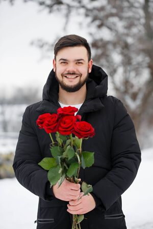 Handsome young man with red roses in hands outdoors in snowy weather. The concept for St. Valentine's Day Foto de archivo - 138047436