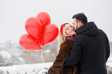 Young beautiful couple with red roballs outdoors in snowy weather Foto de archivo - 138047446