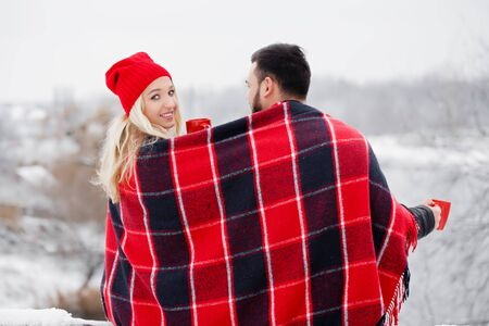 Young beautiful couple at a picnic in winter they drink coffee Archivio Fotografico - 138047213