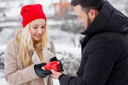 A guy gives his girlfriend a heart-shaped box, a concept for Valentine's Day Foto de archivo - 138047409