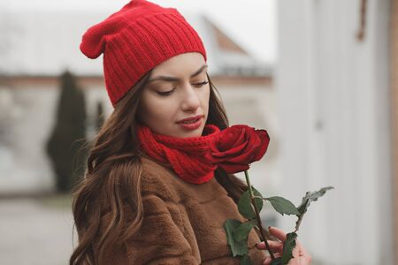 Beautiful brunette with red rose in her hands. The concept for St. Valentine's Day Foto de archivo - 138047497