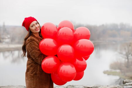 Beautiful girl holds a Balloons in her hands. The concept for St. Valentine's Day Foto de archivo - 138047775