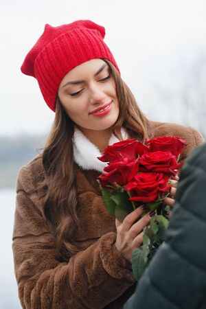 Young beautiful couple with red roses outdoors Foto de archivo - 138047644