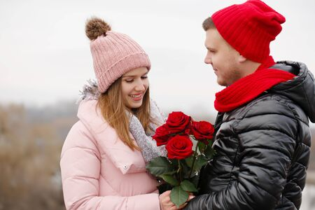 Young beautiful couple with red roses outdoors Foto de archivo - 138047689