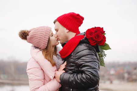 Young beautiful couple with red roses outdoors