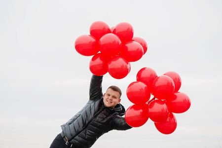 Young man with red balloons in his hands. The concept for St. Valentine's Day Foto de archivo - 138047529