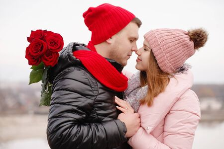 Young beautiful couple with red roses outdoors Foto de archivo - 138047740