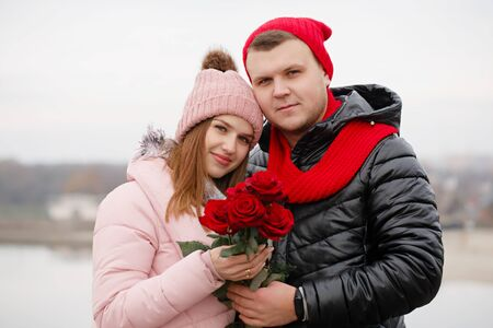 Young beautiful couple with red roses outdoors Foto de archivo - 138047570