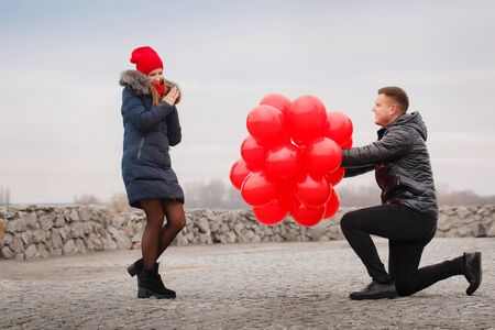 Young couple walking with red balloons. The concept for St. Valentine's Day Foto de archivo - 138047532