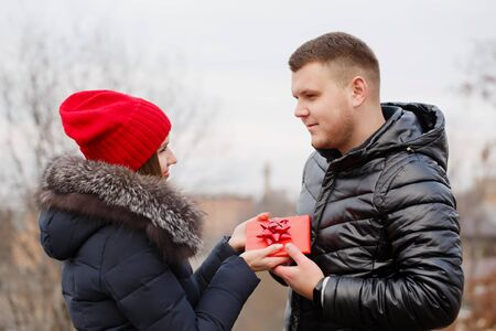 Young couple with a gift in their hands. The concept for St. Valentine's Day