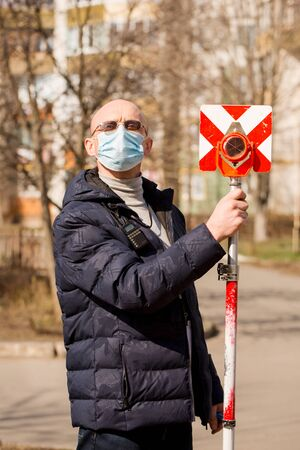 Surveyor holds a geodetic reflector in a protective mask. Coronavirus Protection Concept