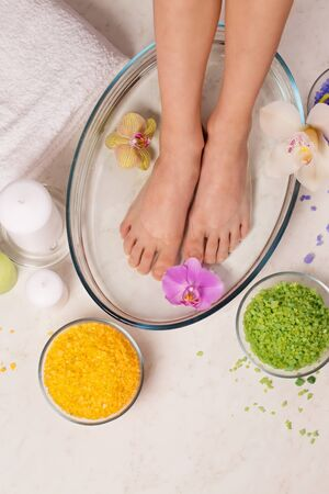 Small female legs in a salt bath, energetic cleaning of legs in Reiki stream