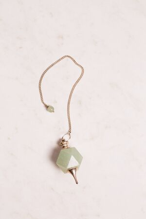 pendulum made of natural stone for work in a stream reiki