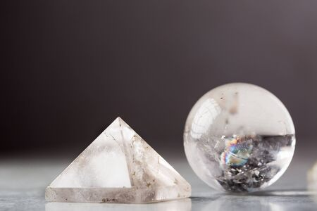 crystal ball and rock crystal pyramid against a dark background, Reiki concept