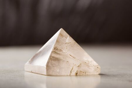 Natural rock crystal pyramid against a dark background, Reiki concept