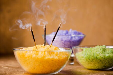 incense sticks and sea salt for a session of energy cleansing legs in a stream of reiki Archivio Fotografico