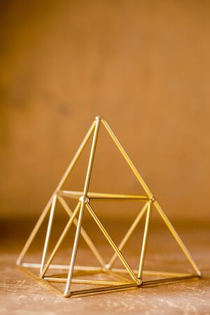golden pyramid of wishes on a golden background Stockfoto