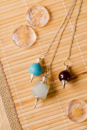 Pendulums for working in a reiki stream and signs of the second stage of a reiki on rock crystal Archivio Fotografico