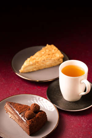 various cakes with a cup of tea on a burgundy background