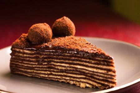 Spartak multilayer chocolate cake on a burgundy background
