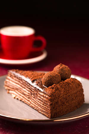 Spartacus multilayer chocolate cake with a cup of coffee on a dark background