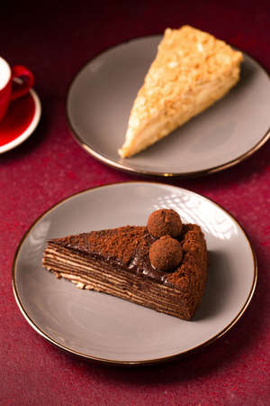 various cakes with a cup of coffee on a burgundy background Stock fotó