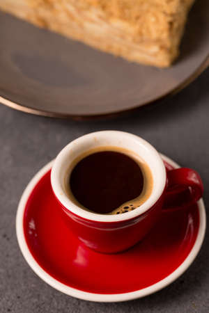 coffee expresso in a red coffee cup with a slice of delicious napoleon cake