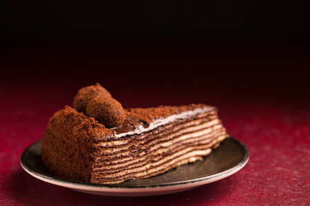 Spartacus multilayer chocolate cake on a burgundy background