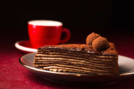 Spartak multilayer chocolate cake with a cup of coffee on a dark background