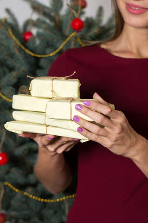 Girl with gifts on the background of a christmas tree
